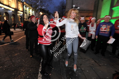 SWANSEA / Copyright Adrian White Friday 16th December 2016 Revellers dance to the Pheonix Choir in Wind Street, Swansea celebrating Christmas on Black Friday.