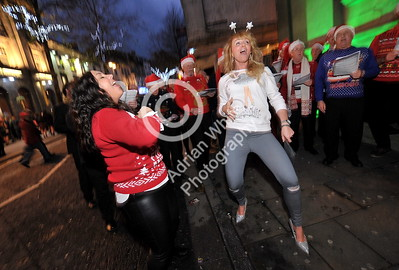 SWANSEA / Copyright Adrian White Friday 16th December 2016 Revellers dance to the Pheonix Choir in Wind Street, Swansea celebrating Christmas on Black Friday.  BYLINE www.click4prints.com