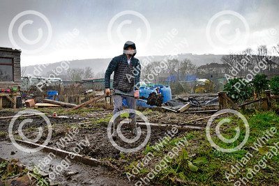 Allotmenteers in Pontypridd begin the clean up of their growing space following the wreckage to the Tin Plate Allotments by the burst banks of the River Taff brought by the rain and floods of Storm Dennis.  Tin Plate Allotmenteer Aarran Lacey makes good his beds as another heavy downpour begins.  Copyright © 2020 by Adrian White  Photography, all rights reserved. For permission to publish - contact me via www.adrianwhitephotography.co.uk Please respect copyright laws.