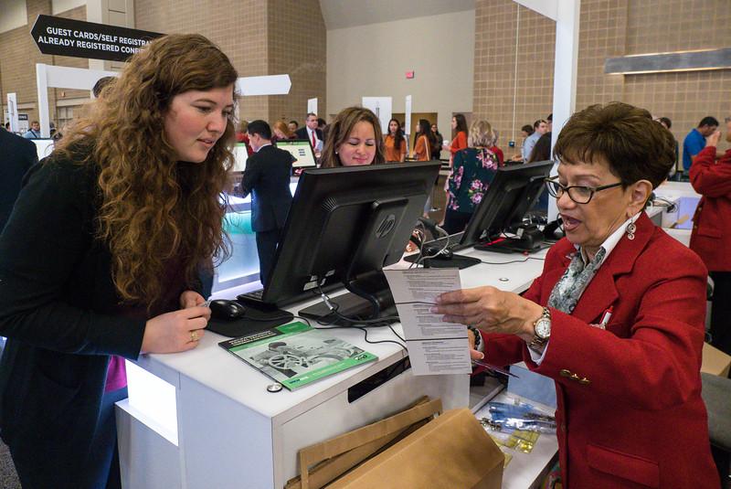 Attendees get their badges registration desk