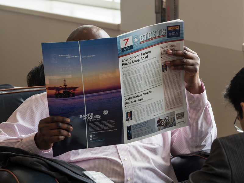 Attendees read daily newspaper during breaks