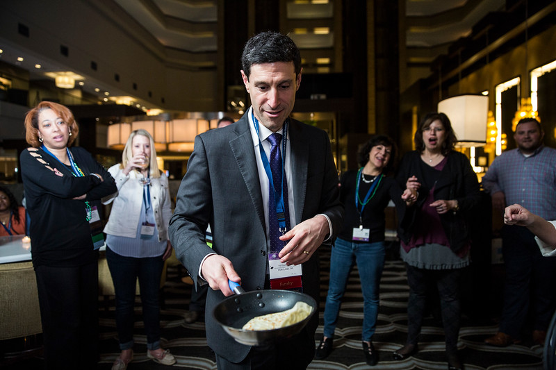 Attendees learn to flip crepes at the Patient Navigator Focus MI Diplomat Dinner during the ACC Quality Summit