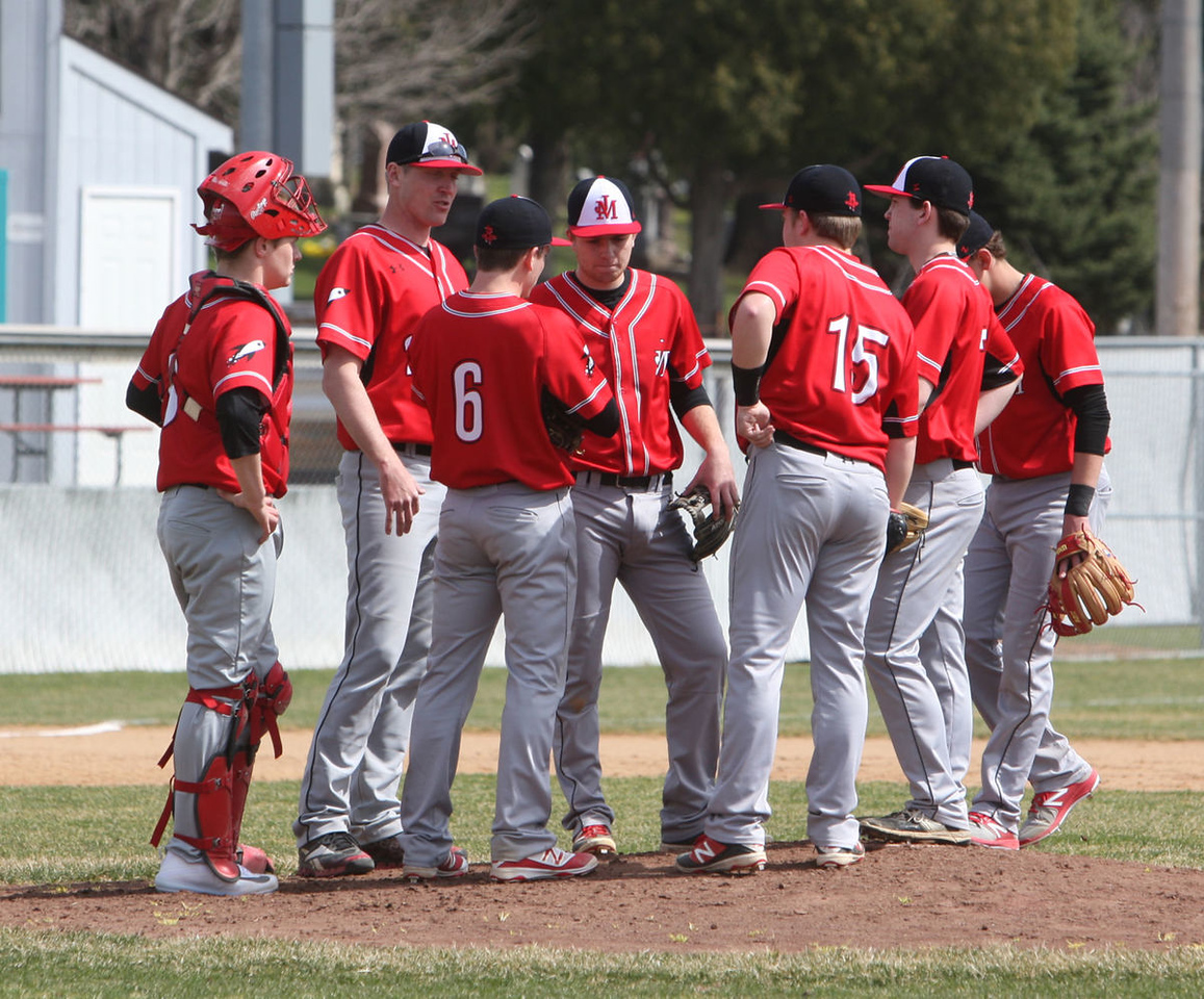 The Rockets meet at the mound during their Saturday game against Duluth East