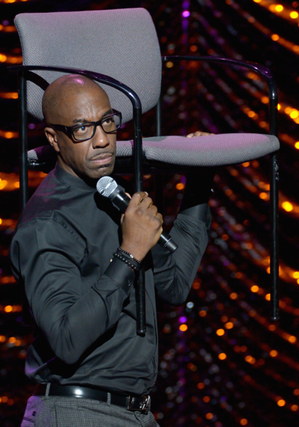 JB Smoove fashions a serving tray out of a chair as he plays the part of a waiter in his act.