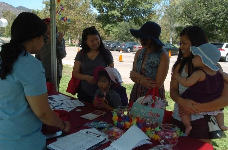 IMF's Communication Associate Sapna Kumar shares educational materials with picnic attendees.