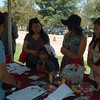 IMF's Communication Associate Sapna Kumar shares educational materials with picnic attendees.