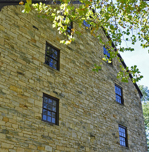 Blue skies reflecting in the west-facing facade of the George Washington Gristmill