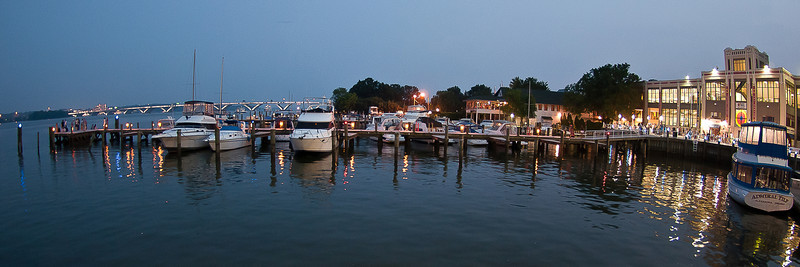 Along the waterfront of Old Town Alexandria, VA at night with the Wilson Bridge in the far distance over the Potomac