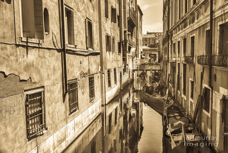 Gondolas lie waiting in a narrow Vencian backwater canal.<br /> <br /> Late afternoon gold mottles the texture of the old walls and melts into the aqua water.