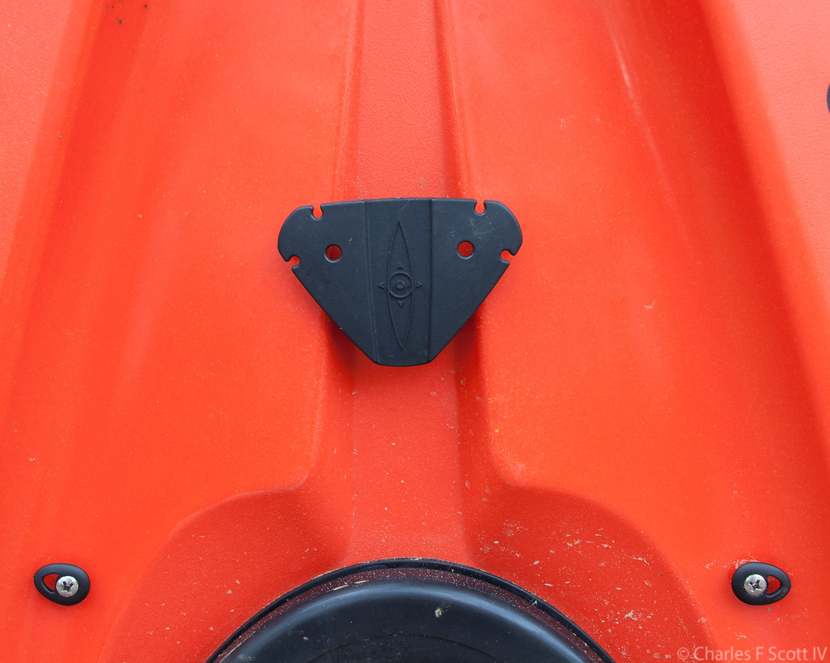 The rudder strings from the peddles in the forward section go in the holes in the triangle piece. The loops go around the notches at the upper corners. The two black plastic pieces at the bottom are guides for the strings.