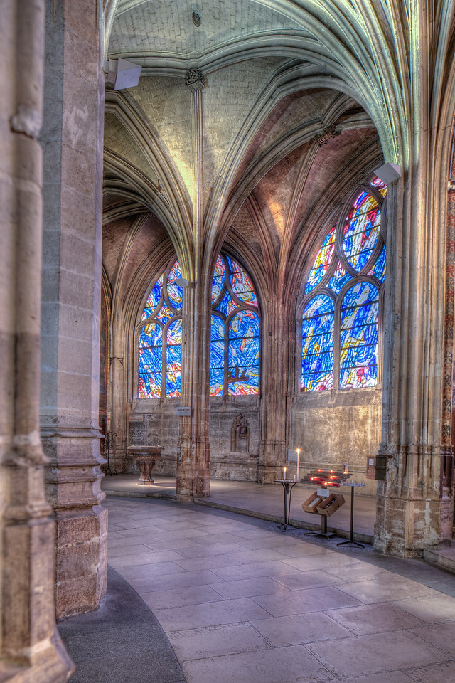"""The rounded space behind the choir is formed of a double ambulatory delimited by concentric semi-circles of columns.   Originally the ambulatory served to channel the flow of crowds moving around the church without disturbing ceremonies taking place at the altar.   In the Saint Séverin setting the central coiled column is the most dramatic feature of the circular passageway, but this striking shaft is surrounded by a veritable forest of others, each column differing from its neighbor while stamped by its own specific design, terminating in a spray of ribs that spread out to form the vaults.   <br />  The captivating visual effect of this harmonious symphony of columns led imaginative commentators of the past to describe the ambulatory of Saint Séverin as a """"palm grove"""" with its crowd of vertical shafts and overhead arched branches.  <a href=""""http://www.saint-severin.com/"""">http://www.saint-severin.com/</a>"""