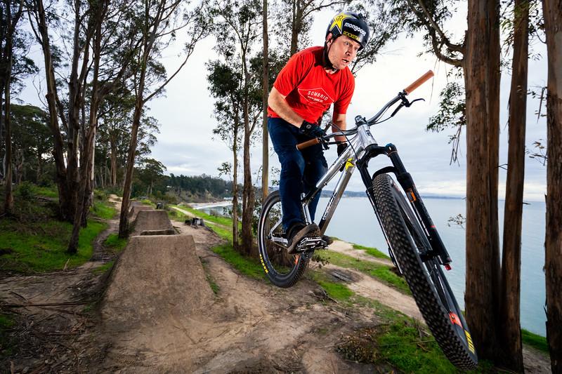 Greg Watts with a barspin at a classic Santa Cruz dirt jump spot.