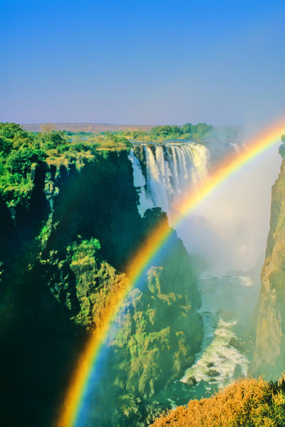 View of Victoria Falls from near the visitor center on the Zimbabwe side. The raibow is caused by the fine spray coming up from the base of the gorge.