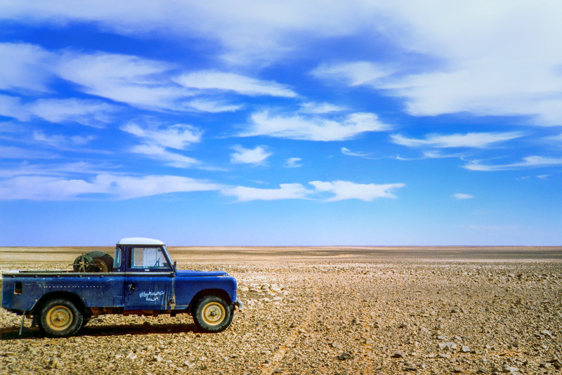 Land Rover on the gravel plain at the Algerian border, south of Ghadamis, Libyan Desert