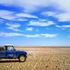 Land Rover on the gravel plain at the Algerian border, south of Ghadamis, Libyan Desert