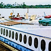 Three riverboats sit at the jetty on the Batam Barang in Sarawak. Note the spare propellors lashed to the deck on each boat. 1989.