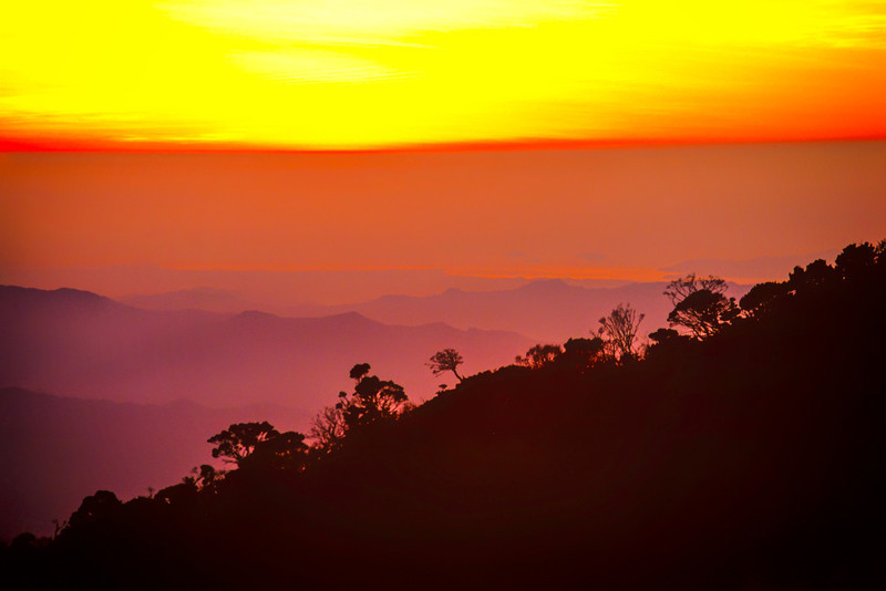 The sun has slipped below the horizon of the South China Sea in this photo taken in 1989 from Laban Rata on Mount Kinabalu. On the right you can make out the island of Pulau Gaya and the three smaller islands of Pulau Manukan just to the south (left). On the shoreline lies the town of Kota Kinabalu invisible in the haze. The coast is some 40 miles (60 km) distant from my shooting location.