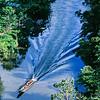 A longboat motors up a river in the Gunung Mulu National Park. 1989.