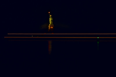 Statue of Liberty With Passing Boat Light Trails