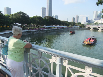 Walking across a bridge across the Singapore River (the bridge was actually built in the late 1800s) - Mom stops to watch a tour boat and a bumboat pass by