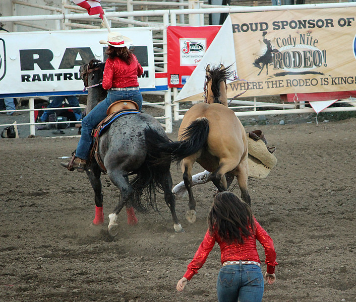 A night at the rodeo. Cody, Wyoming.<br /> Opening ceremony excitement results in a spooked horse and cowgirl on the ground.