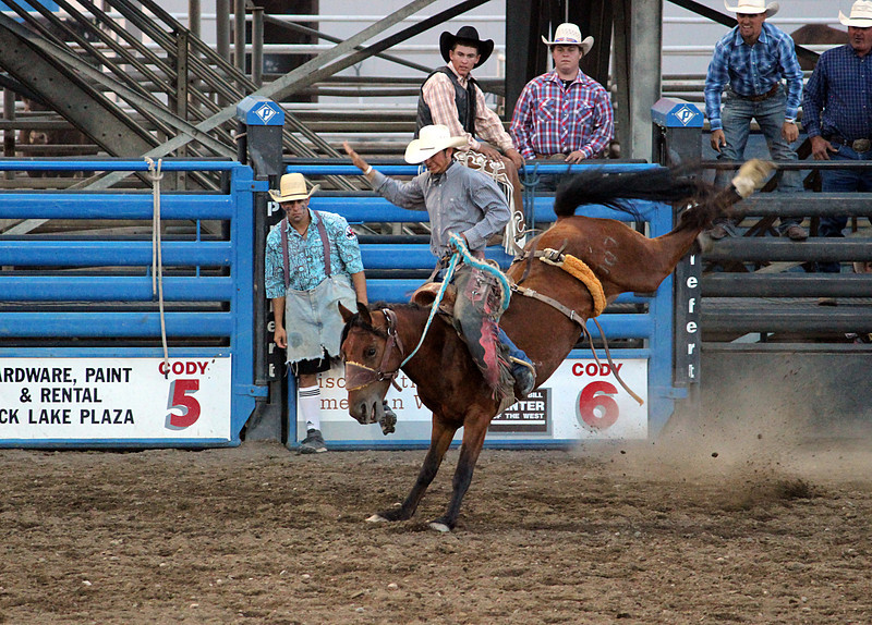 A night at the rodeo. Cody, Wyoming.<br /> Saddle bronc taking a cowboy for a ride.