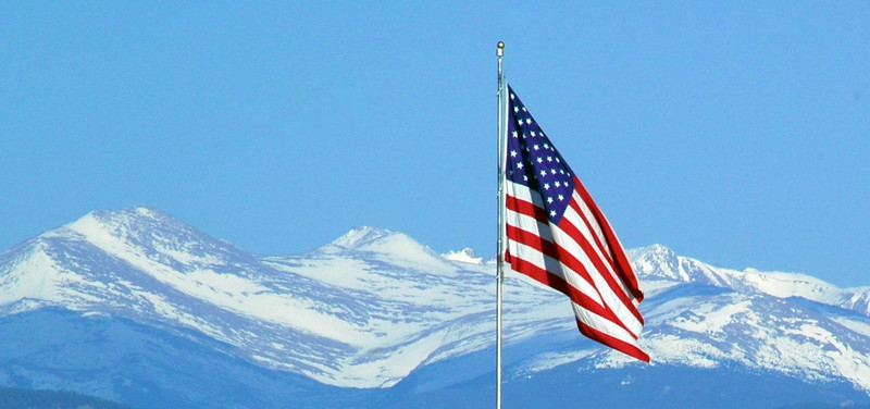 Old Glory stands tall in Loveland against a Beautiful Rocky Mountain National Park background.