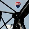 Historic bridge iron frames the lightness of a balloon launch.