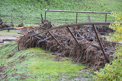 Without new- and- old-growth grass, pine needles, thickets, and roots to slow runoff, heavy rains caused damage to corrals and fences. (Gaylene Fortner photo)
