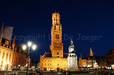 Evening shot of the Belfry (Belfort) and Cloth Hall (Lakenhalle) on the Market Square (Markt). In front of the image is the statue of Jan Breydel and Pieter de Coninck who laid the foundation for the citizens' uprising which lead to the Battle of the Golden Spurs.