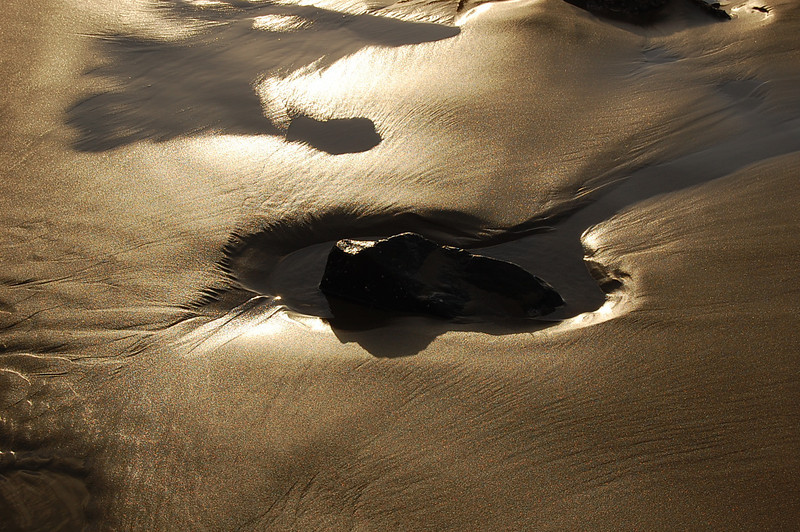 Fading sunlight plays on sand and water
