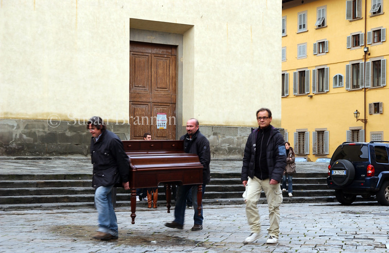 Moving a piano in the city center of Florence, Italy