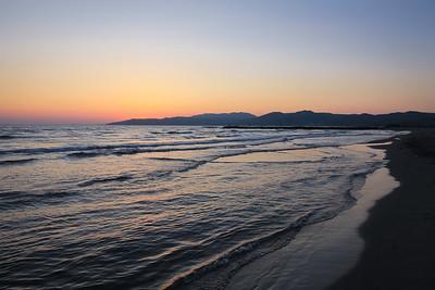 The sun sets on the Aegean Sea in Kuşadası, Turkey.