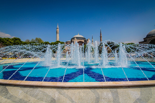 The Hagia Sophia peeks out above a fountain located in the large promenade separating it from the Blue Mosque in Istanbul