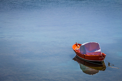 Orange boat on blue water.
