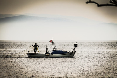 Lone fisherman casts a net off the coast of Cunda Island, near Ayvalık, Turkey.