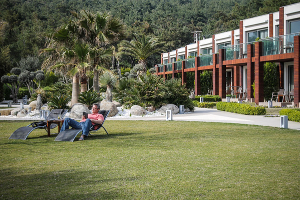 Resting and reading on the peaceful grounds of Ortunç Hotel on Cunda Island, Ayvalık, Turkey.