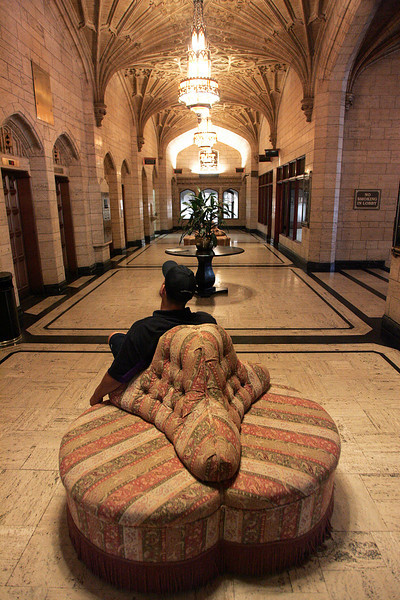 A Fed-EX delivery man relaxes in the Philtower lobby while waiting for an elevator.