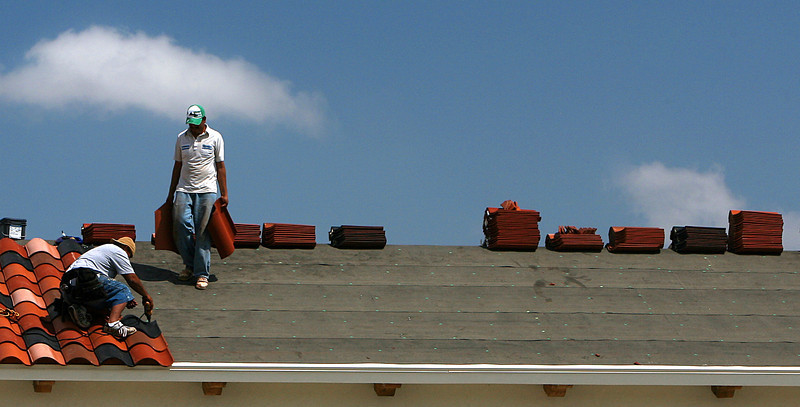 Workmen tile the roof of the Plaza Del Sol Shopping Center in South Tulsa Thursday.