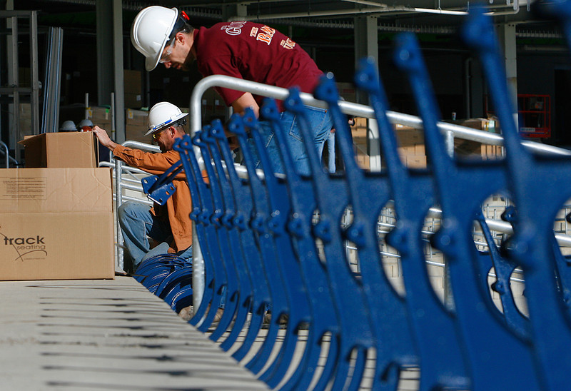 Rick Chenault and Jesse Fix install some of the first of the approximately 5800 seats planned for the ONEOK Field in Tulsa.
