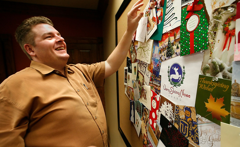 Greg Rex of Rex Public Relations tacks up Christmas cards received as part their ìVery Shiny Nose Awardî competition.  The firm is sponsoring the competition to find the most creative Christmas card and is also donating $5 dollars per entry to  Tulsa Day Care for the Homeless.