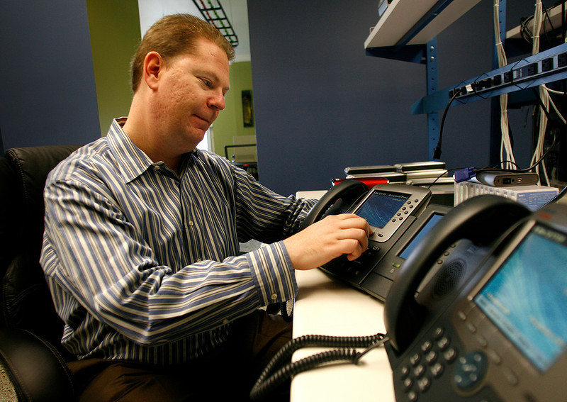 Tim Jackson, Owner of Jackson Technical, quality checks a customerís office phone setup.