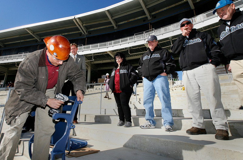 The first seat at ONEOK Field in Tulsa is installed by Melvin Zacaris as Tulsa Drillers President Chuck Lamson and several season ticket holders look on.