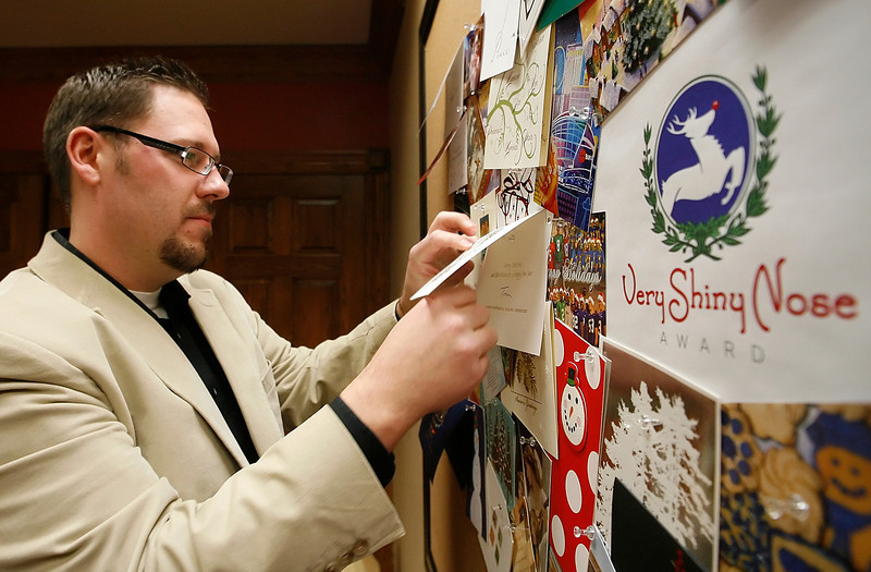 Steve Rex of Rex Public Relations tacks up Christmas cards received as part their ìVery Shiny Nose Awardî competition. The firm is sponsoring the competition to find the most creative Christmas card and is also donating $5 dollars per entry to  Tulsa Day Care for the Homeless.