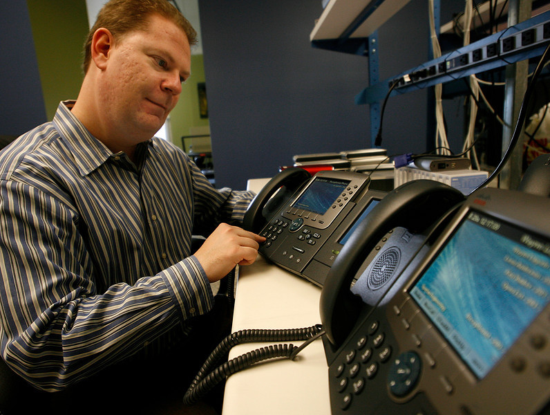 Tim Jackson, Owner of Jackson Technical, quality checks a customerís office phone setup.