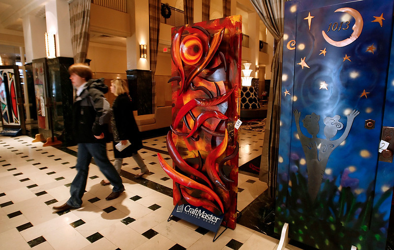 Guests of the Mayo Hotel walk by painted door on display in the lobby.