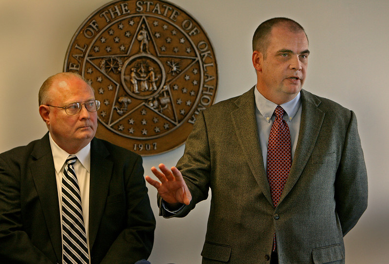 Manager of Consumer Education Jim Palmer looks on as Bennett Abbott, Chief of Telecom with the Oklahoma Corportation Commission speaks at a Tulsa press conference to ask the public to comment on two options available to charge the current area code systems.