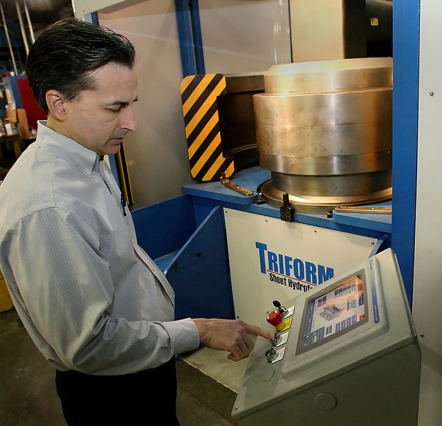 Scott Pryer of Tulsaís Pryer Technology Group loads plate metal into a prototype Hydro forming press his company is offering