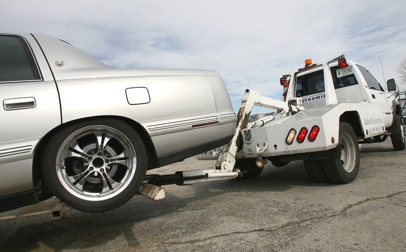 **** Adjust Cutline to fit the story **** In a simulated vehicle repossession Baker Recovery employee hoists the car before leaving.