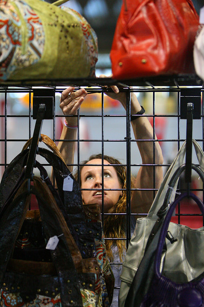 Avenue Handbags employee Whitney Crawford sets up a display of bags for the Womenís show in Tulsa.